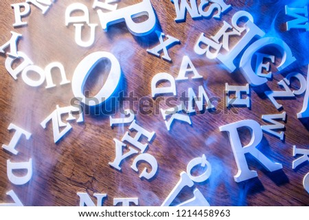Letters of the Latin alphabet on the table. White Latin letters. Latin alphabet in smoke.