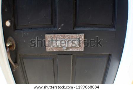 letters sign slot on black door #1199068084