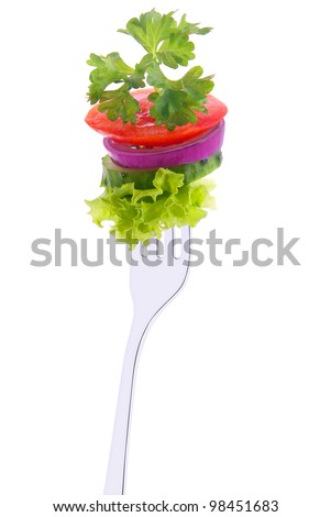 lettuce, cucumber, onion, tomato and parsley on a fork isolated on white background.