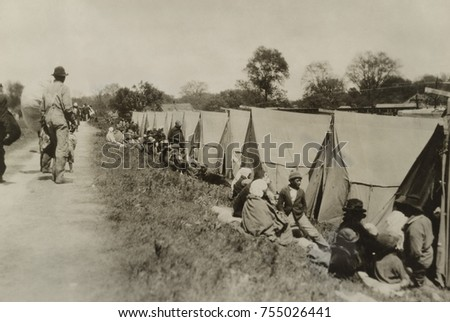 Levee at Greenville, Mississippi, where African Americans sit by tents on uneven ground. The tents were supplied by the American Red Cross. With no established emergency response force, the U.S Congre Photo stock ©