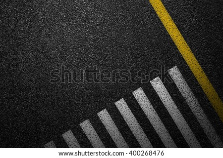 Level asphalted road with a dividing stripes and pedestrian crossing. The texture of the tarmac, top view.