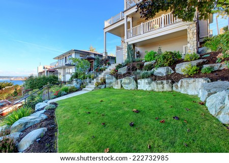 Leveled landscape design with rocks and flowers, bushes and trees. Real estate in Tacoma, WA