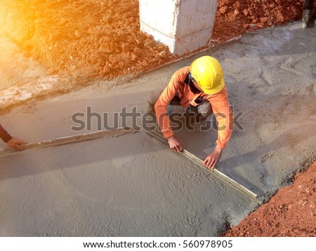 Leveling concrete with trowels, laborer spreading poured concrete. Selective focus. A construction worker is pouring cement and concrete.