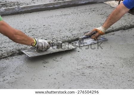 Leveling concrete with trowels, mason hands spreading poured concrete. Selective focus.
