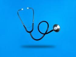 Levitating stethoscope on blue background and shadow under it. Stock photo.