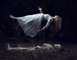 Levitation image of a woman rising from a skeleton on some dead leaves