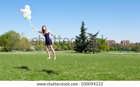 Levitation of beautiful girl with balloons.