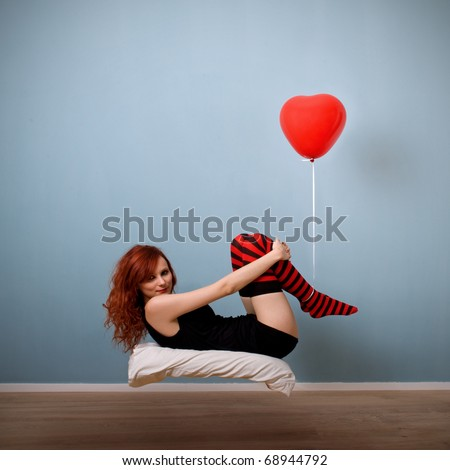 Levitation portrait of beautiful red caucasian girl with heart balloon.