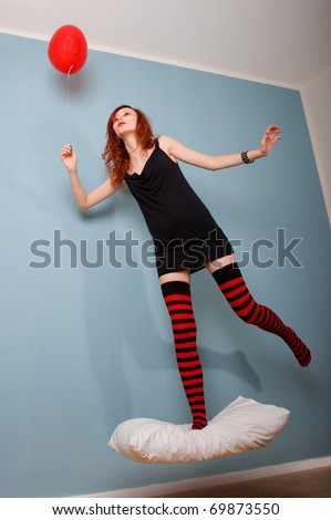 Levitation portrait of beautiful redhead caucasian girl with heart balloon.