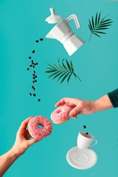 Levitation surrealist image, coffee and two pink doughnuts in hands. Flying coffee beans. ceramic coffee maker and espresso cup. Vibrant, trendy, bold green mint color background with palm leaves.