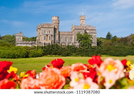 Lews Castle in Stornoway, United Kingdom with blurred roses in foreground. Castle with green grounds on blue sky. Historic architecture and design. Landmark and attraction. Summer vacation on isle. Zdjęcia stock ©