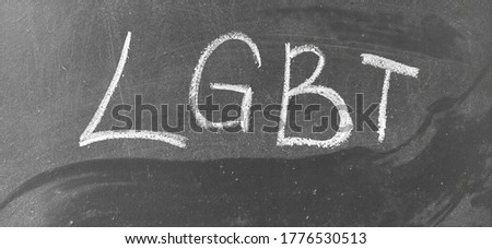 Photo of LGBT, abbreviation for LGBT. A symbol of free love. Hand written letters in white chalk on a school blackboard. Black and white monochrome image