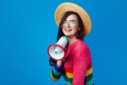 Lgbt activist girl in rainbow sweater speaking in megaphone and smiling