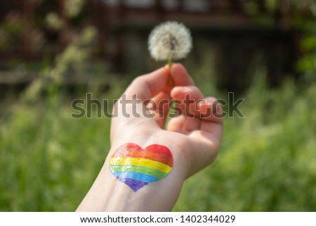 LGBT flag rainbow heart shape on hand with dandelion #1402344029