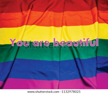 "LGBT flag with phrase ""You are beautiful"" in pink at the center of composition. #1132978025"