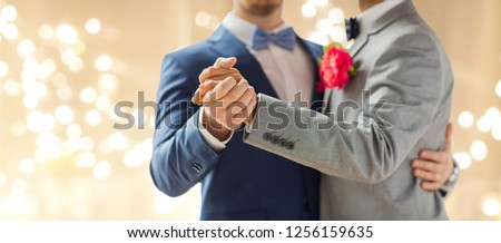 lgbt, homosexuality and same-sex marriage concept - close up of happy male gay couple holding hands and dancing on wedding over festive lights background #1256159635