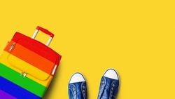LGBT pride people travel banner, gay, lesbian etc summer holidays, vacation concept, tourism, suitcase LGBTQ community flag color, blue gumshoes, rainbow bag, shoes, yellow background, text copy space