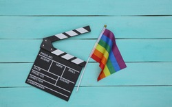 Lgbt rainbow flag, movie clapper board on blue wooden background. Tolerance. Cinematography, filmmaking. Top view.