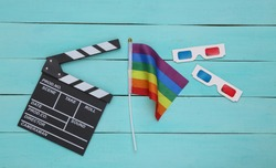 Lgbt rainbow flag with 3d glasses, movie clapper board on blue wooden background. Tolerance. Cinematography, filmmaking. Top view.