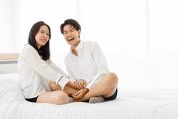 LGBTQ couple lovers, a handsome girl as man or butch and femme, spending and sharing loving time in white bedroom with fun, warmth, and happiness.