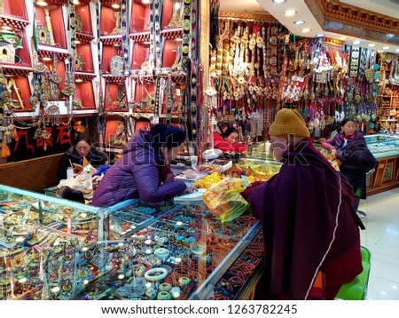 Lhasa, China - December 12 2018: Buddhist monks looking at Tibetan handicrafts in a traditional market on Bohkar street in Lhasa in Tibet, China #1263782245