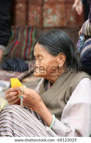 LHASA, TIBET - SEPTEMBER 25: unidentified pilgrim woman reads prayer flag to show her piety to Buddha and meditate on the threshold of the Jokhang Temple on September 25, 2009 in Lhasa, Tibet, China