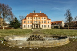 Libechov, old abandoned baroque castle in central Bohemia,Czech republic.Romantic building with balcony,red facade and empty fountain in nearby park.Rebuilt in 16th century as Renaissance chateau
