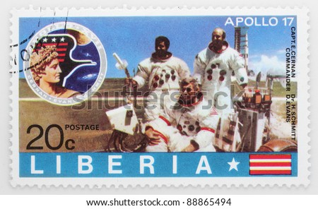 LIBERIA - CIRCA 1975: A stamp printed in Liberia shows astronauts E. Cernan,  H. Schmitt and D. Evans on the LRV Rover against spaceship Apollo 17, circa 1975.