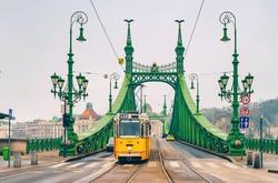 Liberty Bridge (Freedom Bridge) in Budapest across the Danube River. Historic tram on the bridge.