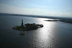 liberty statue photo  made in a helicopter shows the statue located on an island with the horizon and the blue sky in the background and the sun reflecting in the sea