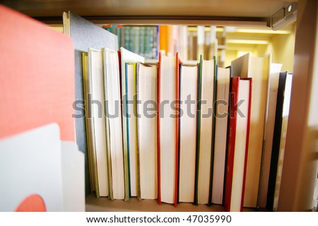 Library books on a shelf, with pages showing