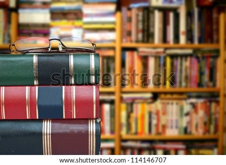 Library concept - Books and glasses against book shelves - stock photo
