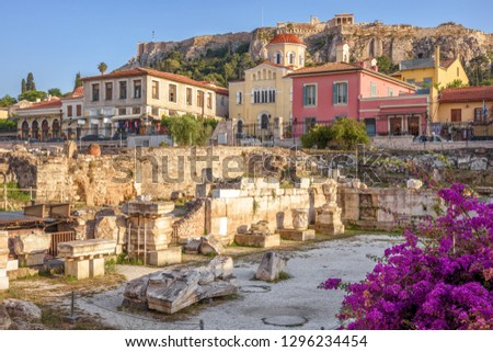 Library of Hadrian overlooking vintage houses and Acropolis, Athens, Greece. Beautiful view of the Athens tourist attractions. Ancient Greek ruins in the Athens center. Scenic cityscape of old Athens.