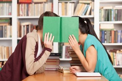 Library romance. Young man and woman sitting close to each other at the library desk and hiding their faces behind a book