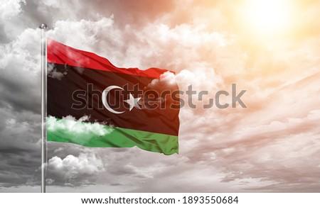 Libya national flag cloth fabric on cloud background. Stockfoto ©