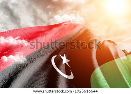 Libya national flag cloth fabric waving on beautiful grey sky. Stockfoto ©