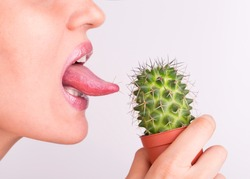 Lick the prickly cactus with your tongue. Cactus needles in the language of a girl. Girl licks tongue prickly cactus.