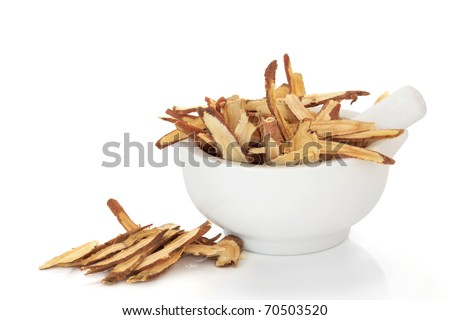 Licorice root in a porcelain mortar with pestle. Used in traditional chinese herbal medicine and for culinary purposes, isolated over white background.
