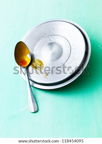 Lid and spoon on green table.