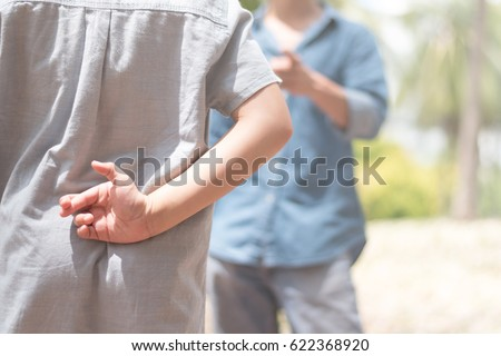 Lie kids concept.Liar female child hand crossing fingers behind back with father in front. lie and cheating, problem child. April Fools