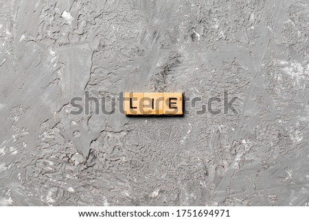 LIE word written on wood block. LIE text on cement table for your desing, concept. ストックフォト ©