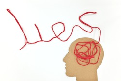 Lies, brainwashing and fake news concept. Human head profile silhouette with red yarn composed into word lies as brain gear.