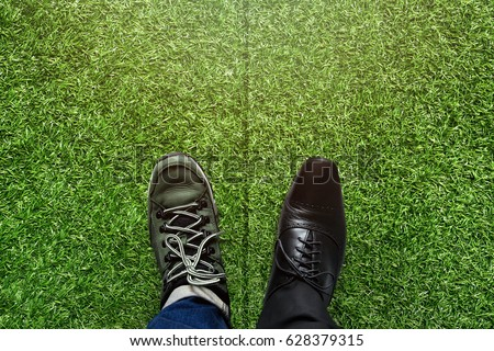 Life Balance concept for Work and Travel present in top view position over green grass field by half of business oxford and adventure shoes #628379315