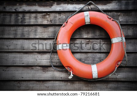 Life Buoy attached to a Wooden Paneled Wall with Plenty of Copy Space