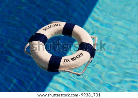 Life buoy floating in the two colored swimming pool in dark and light blue