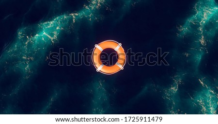 Life buoy. Life buoy in water. Top view of lifebuoy. Life ring floating in a sea. Life preserver in sea. Top view of rescue ring. Rescue ring. Safety ring.
