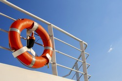 Life buoy on the deck of cruise ship.Security life kit on ship's deck against a clear blue sky.Captured during summer vacations on greek islands