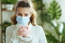 Life during coronavirus pandemic. modern woman in white blouse with medical mask, piggy bank and gloves.