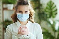 Life during coronavirus pandemic. Portrait of stylish middle age woman in white blouse with medical mask, piggy bank and gloves.
