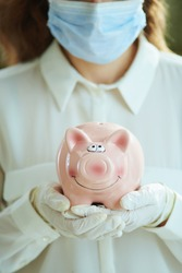 Life during covid-19 pandemic. Closeup on woman in white blouse with medical mask, piggy bank and gloves.